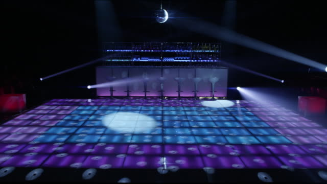 ws nightclub dance floor and bar lit up with flashing lights and disco ball - bar stock-videos und b-roll-filmmaterial
