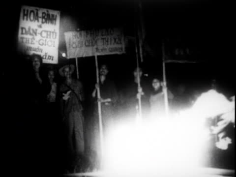 stockvideo's en b-roll-footage met a nightime gathering with a bonfire and cheering / people sign papers and hold signs / molten metal is poured into molds - strohoed