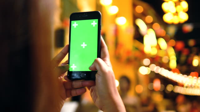 nightlife : hipster woman is holding smartphone with green screen - only teenage girls stock videos and b-roll footage
