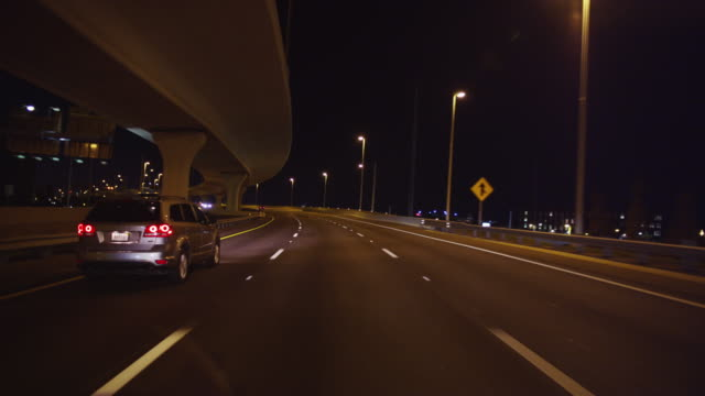 Nighttime POV of a vehicle driving down a four lane urban expressway toward the lights of a city in the distance.