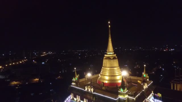 nighttime aerial view of the golden mount at wat saket in bangkok. it is a buddhist temple in pom prap sattru phai district, bangkok, thailand. the... - back lit stock-videos und b-roll-filmmaterial