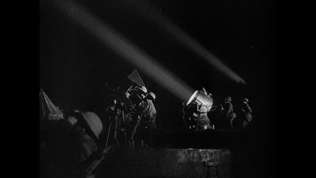 vidéos et rushes de montage night-time air raid, with anti-aircraft guns firing, searchlight blazing, and bombs exploding / london, england, united kingdom - bombardement