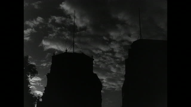 montage night-time air raid, with bomb exploding, anti-aircraft gun flashing, and searchlight blazing / london, england, united kingdom - luftangriff stock-videos und b-roll-filmmaterial