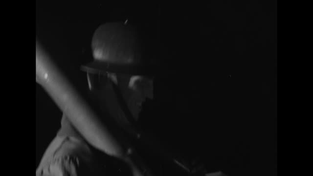 nighttime artillery firing illuminated by spotlights and flashes of the guns a man peers through a viewfinder / note exact month/day not known - artiglieria video stock e b–roll