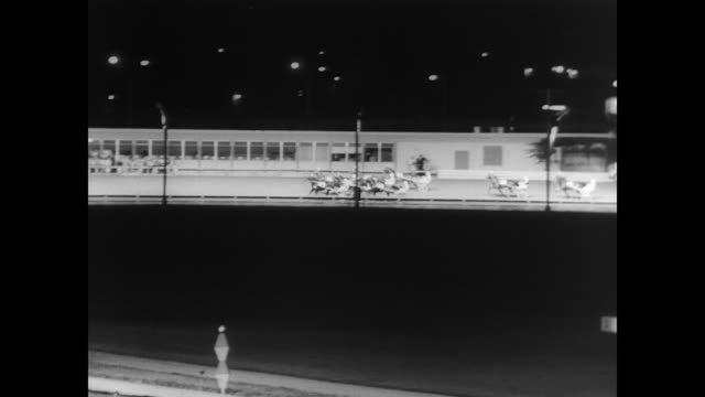 Nighttime at Roosevelt Raceway in Westbury / packed stadium and crowds of people standing about waiting for race to begin / flags from different...