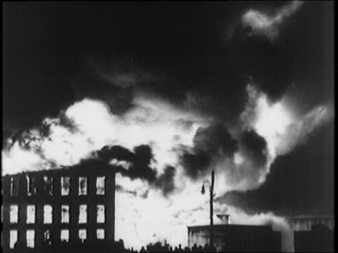 Nighttime blaze smoke and fire / Firestone factory building on fire / various burning building pictures flames seen in every window / fire smoke from...