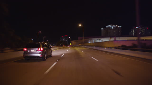 Nighttime POV of car driving down a four lane urban expressway toward the lights of a city in the distance.