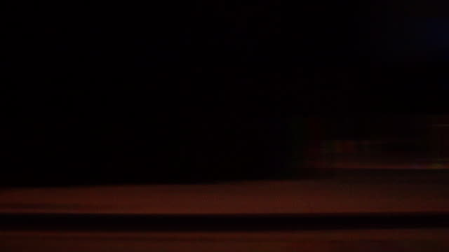 nighttime city streetlights streak by. - tail light stock videos & royalty-free footage