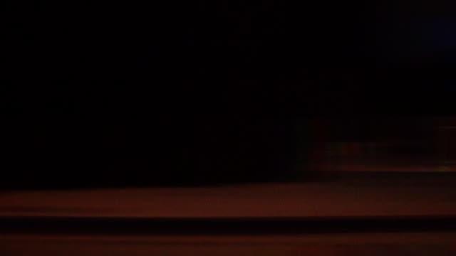 vídeos de stock e filmes b-roll de nighttime city streetlights streak by. - luz traseira de carro