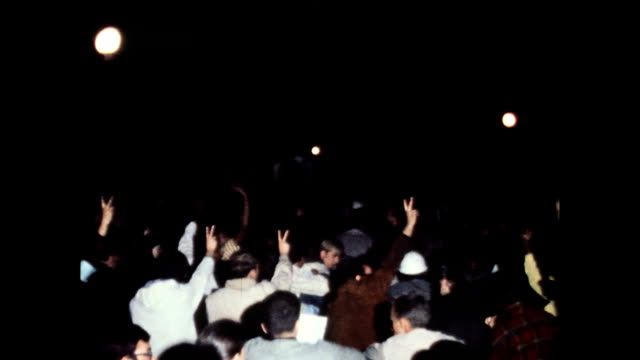 / nighttime crowd during democratic national convention / demonstration crowd in park hippies making peace sign with fingers / police break up crowd... - 1968年点の映像素材/bロール