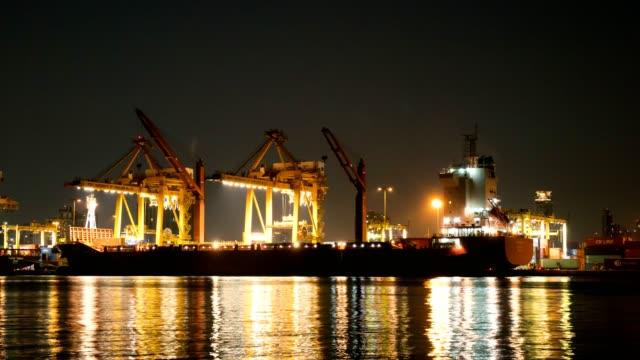 nächtliche industrial container cargo frachtschiff mit arbeitskran flussseite in bangkok thailand. - hafen stock-videos und b-roll-filmmaterial