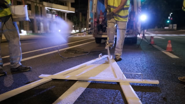nighttime pavement marking crew spray painting turn arrow - roadworks stock videos & royalty-free footage