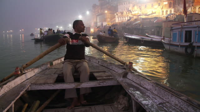 Nighttime shot of a man rowing a boat along the city shoreline in India.