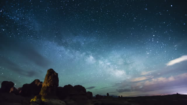 vídeos de stock, filmes e b-roll de a nighttime time lapse from arches national park (near moab, utah), showing the milky way rising over the horizon as it breaks through the low hanging clouds. - utah