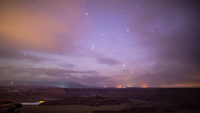 A nighttime time lapse of Dead Horse Point State Park (outside of Moab, Utah) with occasional stars visible through the heavy, low cloud cover and lights clearly visible on the horizon from nearby traffic and towns.