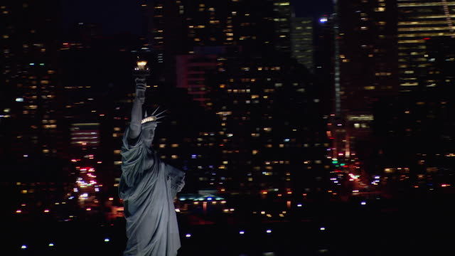 vídeos de stock, filmes e b-roll de nighttime view of lady liberty upholding her flaming torch in new york city. - estátua