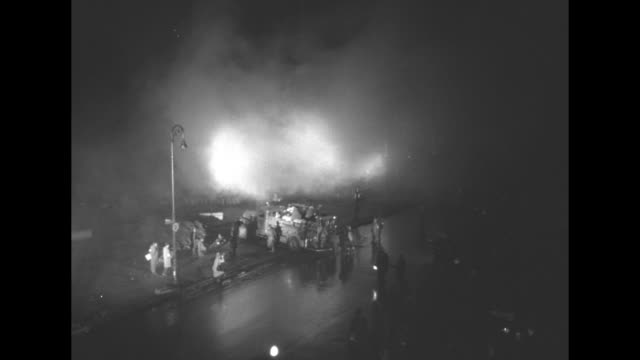 vs nighttime views of whitehelmeted civil defense personnel and civilians walking past illuminated spray of water / billowing smoke in spotlight with... - contatore geiger video stock e b–roll