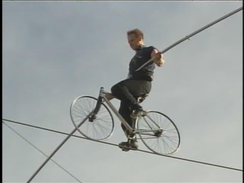 vídeos y material grabado en eventos de stock de nik wallenda gingerly pedals a bicycle on the tightrope above new york city. - pedal