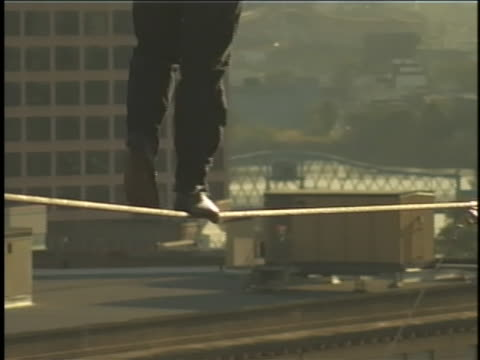 nik wallenda gingerly walks across a tightrope above new york city. - tightrope walking stock videos & royalty-free footage