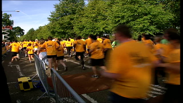 nike 10k 'run london' race sets north vs south; england: london: hyde park: ext runners wearing yellow t-shirts along at start of nike 10k race... - all shirts stock-videos und b-roll-filmmaterial