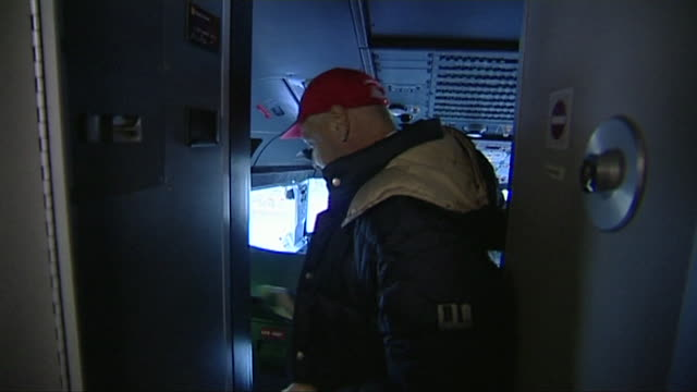 niki lauda arrives in a airplane cockpit removes his coat sits in the seat and prepares to fly the plane - switch stock videos & royalty-free footage