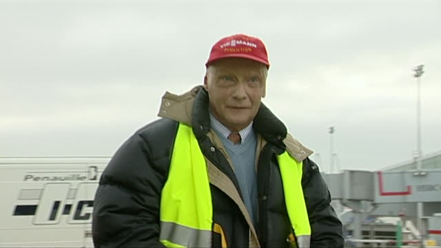 niki lauda leaves a 'lauda air' plane walks down the steps in a yellow high vis black jacket and red baseball cap walks across airport apron greets... - dark stock videos & royalty-free footage