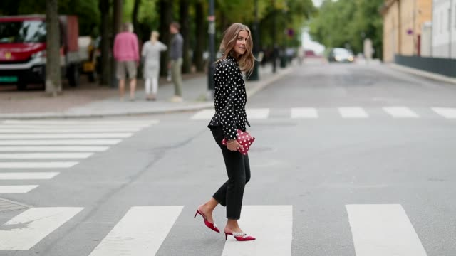 Nina Sandbech wearing cropped pants red clutch and a blazer jacket with strong shoulder line with dots print is seen outside the 'Moire' show during...