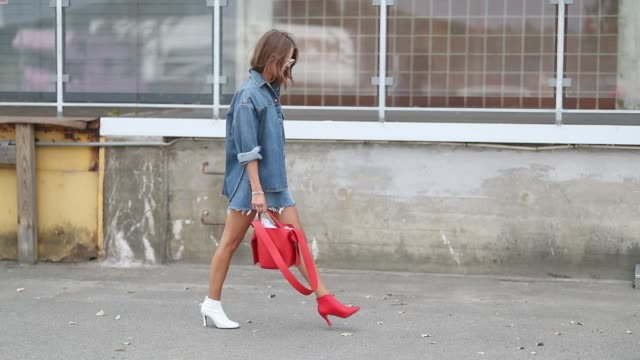 vídeos de stock, filmes e b-roll de nina sandbech wearing red white two tone ankle boots, denim skirt and button shirt is seen outside j.lindeberg during the copenhagen fashion week... - jeans