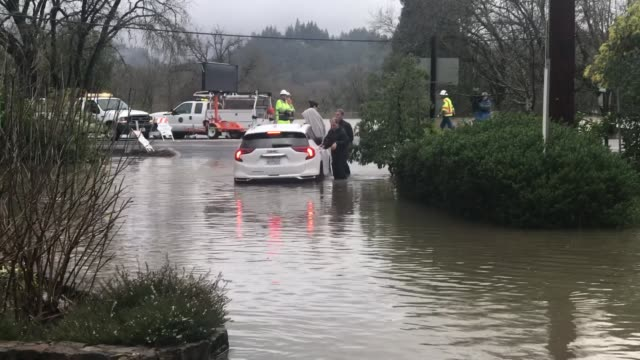 nina sheehan and her husband both from north carolina attempt to drive through the russian river flood waters but get stuck she is pulled out in her... - inn river stock videos and b-roll footage