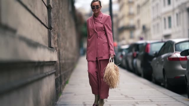 stockvideo's en b-roll-footage met nina suess wears sunglasses, a long pink blazer jacket, a jacquemus rattan fringed bag, flared pants, shoes with burgundy heels, outside elie saab,... - blazer
