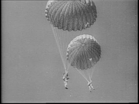 nine planes flying in formation ejecting smoke / soldiers march in long line toward dunes / plane banks in air and parachutes drop / closeup of... - formationsfliegen stock-videos und b-roll-filmmaterial