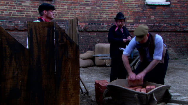 nineteenth century laborers load bricks in the reenactment of the building of a london sewer. - xix secolo video stock e b–roll