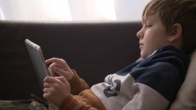 nine-year-old boy uses a ipad as part of online school lessons on the 1st february 2021, bath, england. homeschooling has been a large part of... - digital tablet stock videos & royalty-free footage