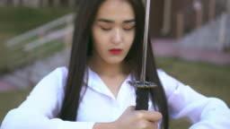 Ninja girl is looking at blade of her katana. Wind blows people's brunette hair.