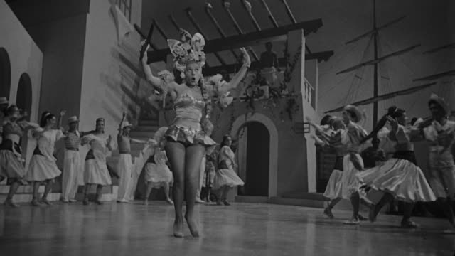 ninon sevilla dancing and singing sassaricando in a big theater with dancers. she is wearing a a short dress and a typical head piece. - 1950 video stock e b–roll