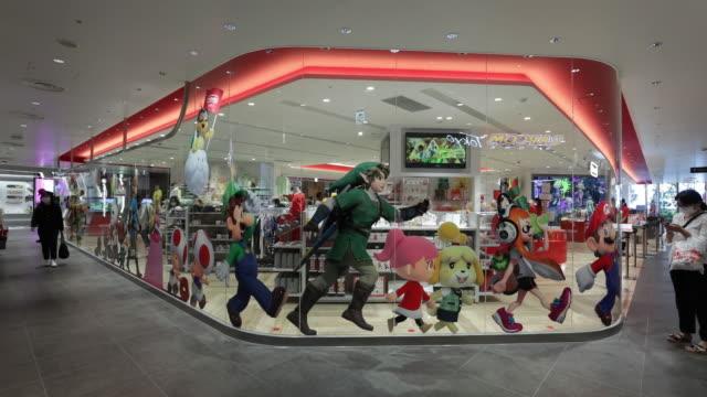 vídeos de stock, filmes e b-roll de nintendo co merchandise sit on display inside the nintendo tokyo store in tokyo japan on tuesday august 4 2020 nintendo is scheduled to report... - sinais de cruzamento