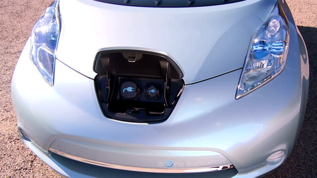 a nissan leaf features electrical ports under the front hood. - electric vehicle stock videos & royalty-free footage