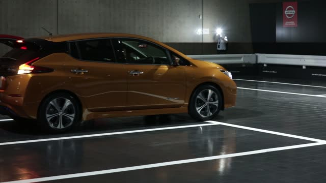 nissan motor co's new leaf electric vehicle is driven during a test drive for the propilot park system at the unveiling in chiba japan on wednesday... - 試運転点の映像素材/bロール