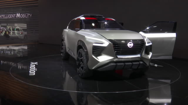 nissan xmotion revolving on turntable / closeup nissan grille logo; zoom out - front end / headlight / front wheel / high angle looking down on on... - head up display parte di veicolo video stock e b–roll
