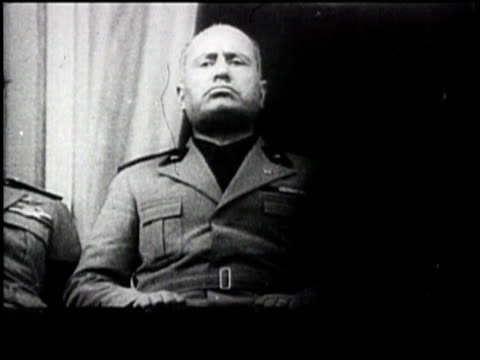 no audio / mussolini delivers a speech in front of a large crowd cheering and waving flags / various shots of mussolini during speech / - benito mussolini bildbanksvideor och videomaterial från bakom kulisserna