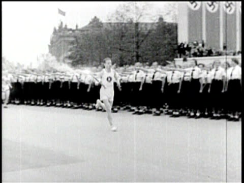 no audio / soldiers on parade bring nazi flags into the olympic stadium / the torch bearer runs past the crowd / carrying the torch / hundreds of... - 1936 bildbanksvideor och videomaterial från bakom kulisserna