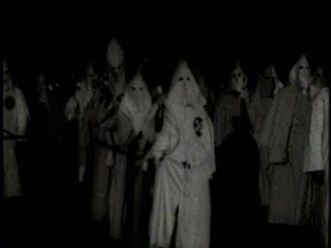 vídeos de stock, filmes e b-roll de 1920 / no audio / the ku klux klan gathers at night / the members wear white robes and a leader wears a black robe / smoke fills the center of their... - ku klux klan