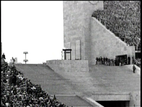 no audio / the torch bearer runs past the crowd / carrying the torch into the stadium / hitler salutes the runner / the torch bearer lights the flame... - 1936 bildbanksvideor och videomaterial från bakom kulisserna