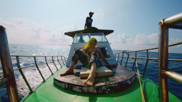 vídeos y material grabado en eventos de stock de nada de mordeduras. una mujer europea activa de 50 años, una turista aburrida, descansa en la cubierta delantera de un pequeño barco de pesca durante el viaje de pesca en alta mar en sri lanka cuando uno de los miembros de la tripulación está sentado y - 50 54 years