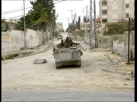 east jerusalem ext israeli soldiers along in armoured vehicles palestinian man carrying shopping bags along past armoured personnel carrier soldiers... - armoured personnel carrier stock videos & royalty-free footage