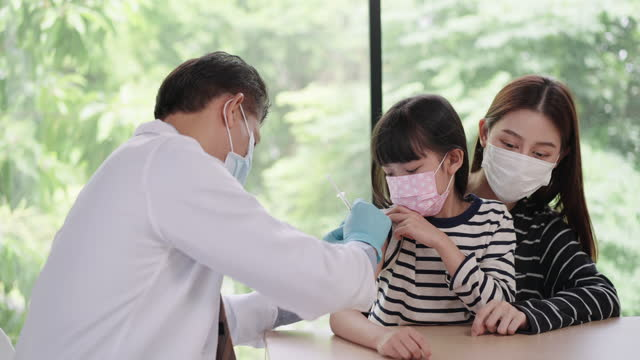 no fears on a needle of daughter and mother, asian senior man doctor applying covid-19 vaccine on asian young teenager girl patient's arm wearing a hygiene face mask, looking at her arm obtaining immune dose with positive emotion, happiness. - dose stock videos & royalty-free footage