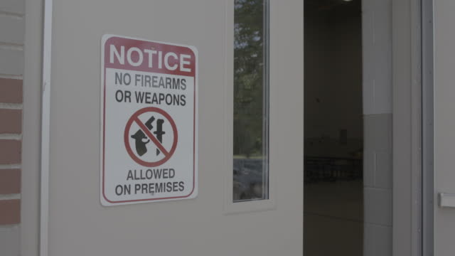 no firearms or weapons sign on building exterior, medium shot - cult stock videos & royalty-free footage