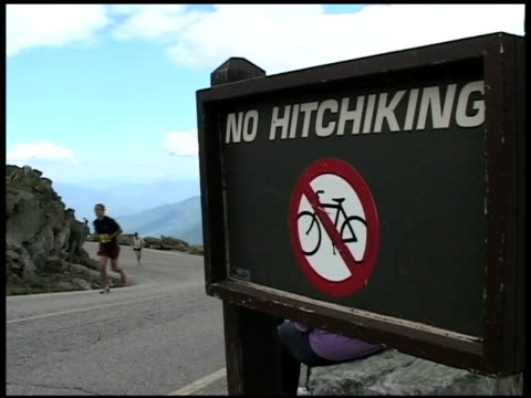 no hitchhiking sign with runners going by from mt washington road race no hitchiking sign with runners going by mountain on july 15 2010 - salmini stock videos and b-roll footage