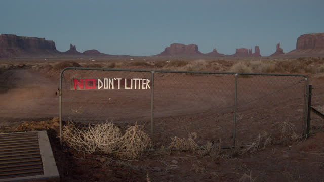 no littering sign, hand-made on a fence in front of the buttes in the monument valley tribal park in northern arizona navajo country - littering stock videos & royalty-free footage