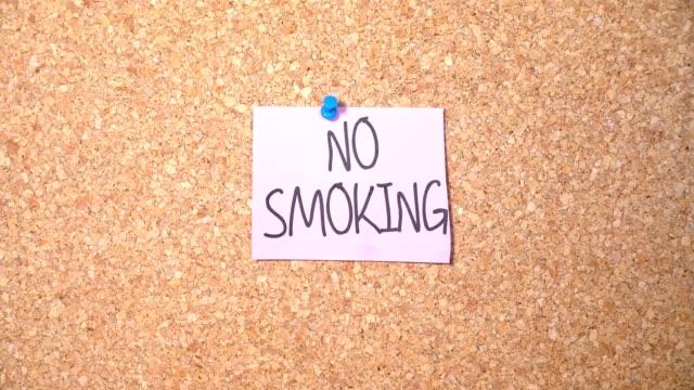 紙を男がコルクボードに固定をしない喫煙単語グループ - 禁煙マーク点の映像素材/bロール